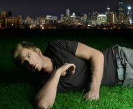 Young man laying on grass. With city in the background Royalty Free Stock Photography