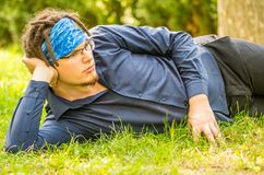 Young man laying on the grass in a park Stock Photo
