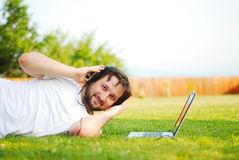 Young man is laying on green ground and taking a n Stock Photo