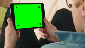 Young man laying on the sofa looking at digital tablet with green screen. Home leisure and fun Young man laying on the sofa looking at digital tablet with green stock footage
