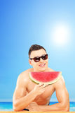 Young man laying on a towel and eating a slice of watermelon Royalty Free Stock Photo