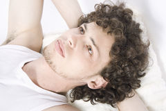 Young man lays on the bed Royalty Free Stock Photography