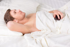 Young man lays in bed and stares at ceiling Royalty Free Stock Photo