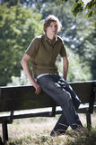 A young man leaning against a bench in a park Stock Photos