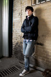 Young man leaning against brick wall Royalty Free Stock Image