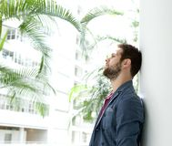 Young man leaning against wall looking away Royalty Free Stock Photo