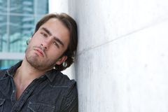 Young man leaning against wall outside Stock Photography