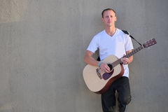 Young man leaning against wall playing acoustic guitar Royalty Free Stock Photos