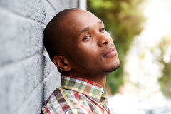 Young man leaning against wall and thinking Royalty Free Stock Photos