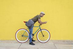Young man leaning on bicycle, using smart phone royalty free stock photography