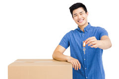 Young man leaning on cardboard box and holding a key Stock Photo
