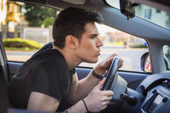 Young Man Leaning Forward on Steering Wheel of Car Royalty Free Stock Image
