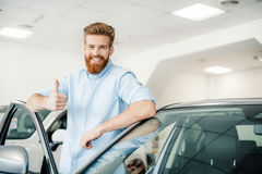 Young man leaning at new car and showing thumb up. Happy young man leaning at new car and showing thumb up Stock Images