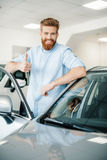 Young man leaning at new car and showing thumb up Stock Photos