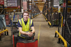 Young man leaning on tow tractor in distribution warehouse stock images
