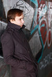 Young man leans back on wall with graffiti Stock Images