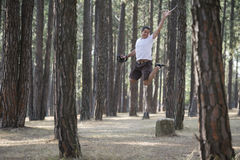 A young man leaps through the trees Royalty Free Stock Image