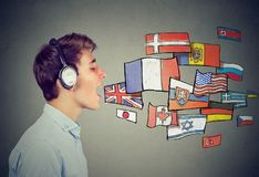 Young man in headphones learning different languages. Young man learning different languages Royalty Free Stock Photos