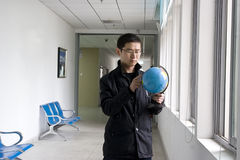 Young man learning globe. Young Chinese man learns the world map in a corridor near window Royalty Free Stock Photo