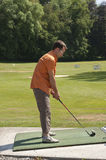 Young man learning golf at the driving range Stock Photos