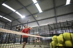 Young man learning how to play paddle tennis with his girl friend Royalty Free Stock Photos