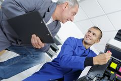 Young man learning to repair photocopier. Young men learning to repair photocopier training Stock Image
