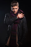 Young man in leather jacket adjusting his scarf Stock Photography