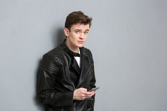 Young man in leather jacket holding smartphone Stock Photos