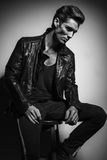 Young man in leather jacket sitting on chair and thinks. Black and white picture Stock Photo