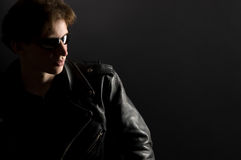 A young man in leather jacket and sunglasses Stock Photography