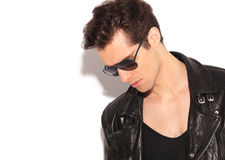 Young man in leather jacket and sunglasses looks down Stock Photo