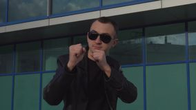 Young man in leather jacket and sunglasses standing in combat pose outdoor.  stock footage