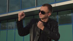 Young man in leather jacket and sunglasses standing in fighter pose outdoor.  stock footage
