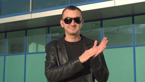Young man in leather jacket and sunglasses standing outdoor and applauding or clapping.  stock video footage
