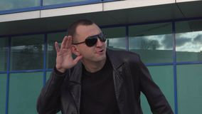 Young man in leather jacket and sunglasses standing outdoor and eavesdropping.  stock video footage