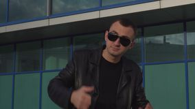 Young man in leather jacket and sunglasses standing outdoor and man inviting someone.  stock video footage