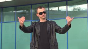 Young man in leather jacket and sunglasses standing outdoor and man inviting someone.  stock footage