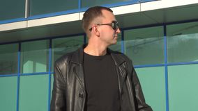 Young man in leather jacket and sunglasses standing outdoor and looking away.  stock video footage