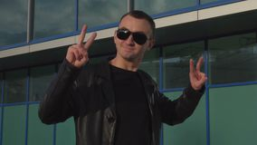 Young man in leather jacket and sunglasses standing outdoor and making peace sign.  stock video footage