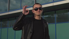 Young man in leather jacket and sunglasses standing outdoor and showing okay.  stock video
