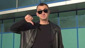 Young man in leather jacket and sunglasses standing outdoor and showing thumb down.  stock footage