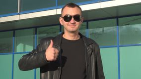 Young man in leather jacket and sunglasses standing outdoor and showing thumb up.  stock footage