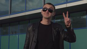 Young man in leather jacket and sunglasses standing outdoor and showing victory sign.  stock footage