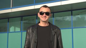Young man in leather jacket and sunglasses standing outdoor and smiles.  stock video