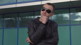 Young man in leather jacket and sunglasses standing outdoor and thinking.  stock footage
