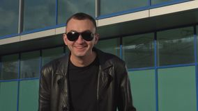 Young man in leather jacket and sunglasses surprised outdoor.  stock footage