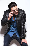 Young man in leather jacket taking off his sunglasses Royalty Free Stock Image