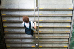 Young man leaving the train station. Young student is leaving the subway station. Perspective from top to bottom. Overhead of grey stairs, urban transportation Stock Photos