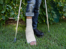 Young man with a leg cast in a garden Stock Photography