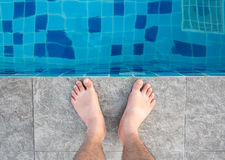 Young man legs standing on border front of swimming pool Royalty Free Stock Images